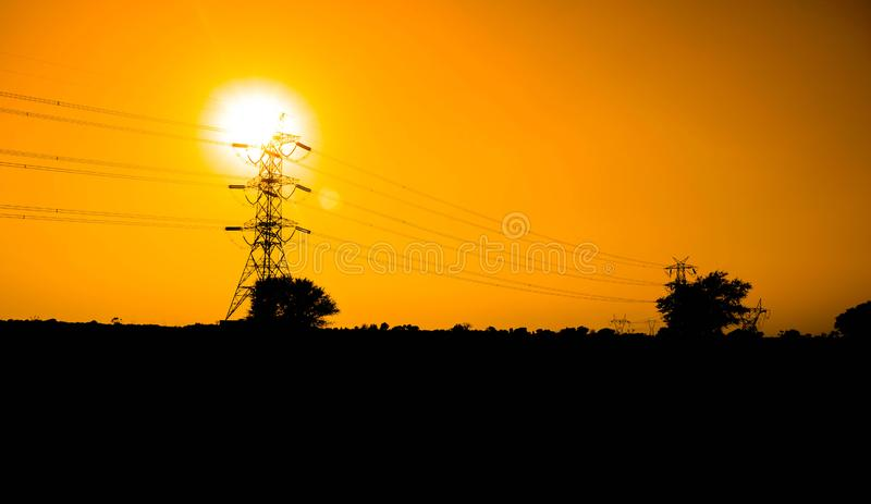 Beautiful sunset over power line with green fields stock image