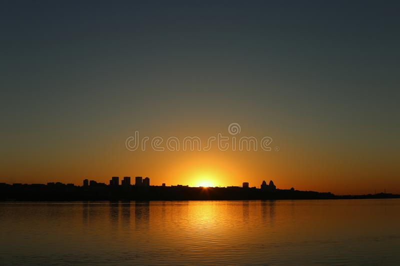 Beautiful sunset over the river with a view of the city, on the horizon. Landscape of the city on sunset royalty free stock photography