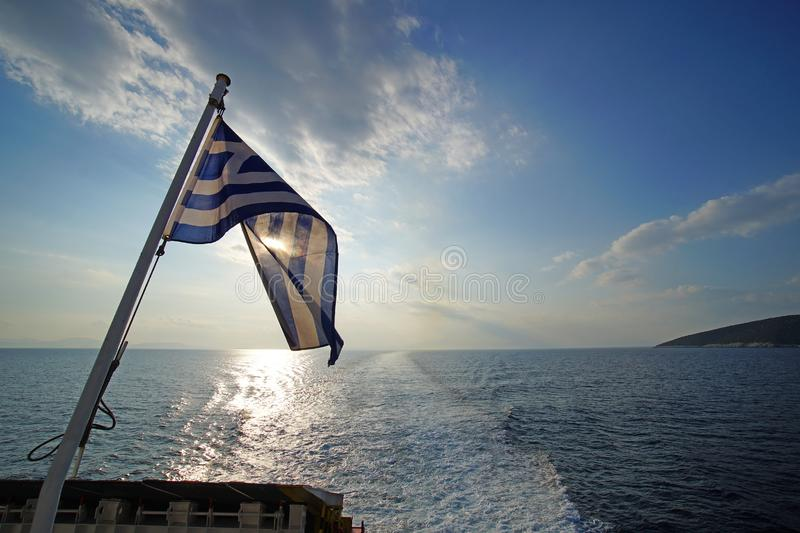 Beautiful sunset over the sea with the Greek flag in the foreground viewed from the ferry on the route to Mykonos in the Cyclades royalty free stock photography