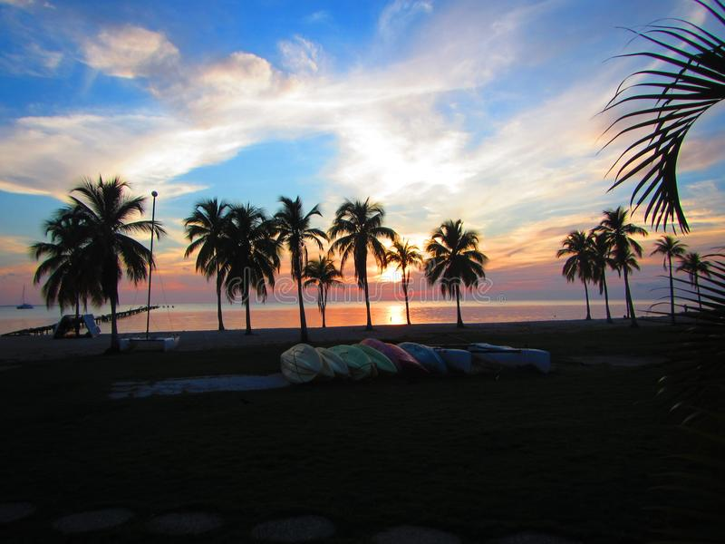 Beautiful sunset over a tropical vacation resort. Isle of youth cuba. Caribbean vacation resort, pool, palm trees, beach, kayaks, boats. Evening sunset royalty free stock photography