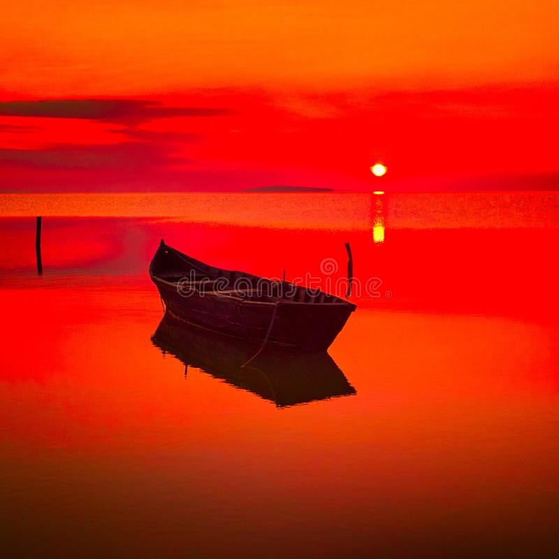 Beautiful sunset over water and silhouette of fishing boat. Beautiful sunset over water and silhouette of wooden fishing boat stock photos