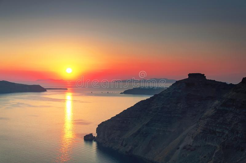 Beautiful sunset overlooking the Aegean Sea, island of Santorini, Greece, Europe. View of the rocks, caldera, volcano, islands, stock photo