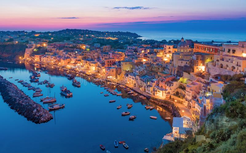 Beautiful sunset in Procida island, Italy. Colorful houses on coastline, fishing and sightseeing boats, cafes and restaurants in Marina Corricella in sunset time royalty free stock image