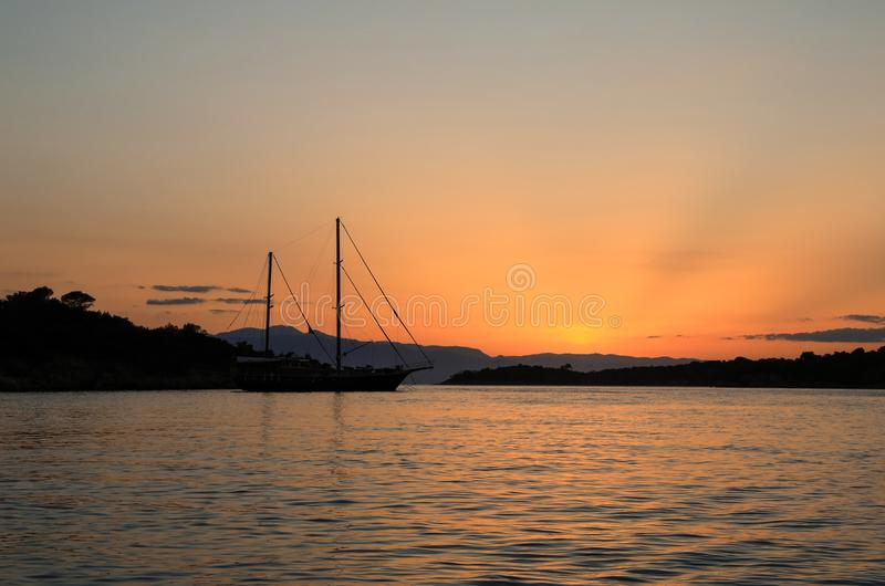 Beautiful sunset sailboat anchoring in a bay near Porto Heli, Peloponnese, Greece. Horizontal stock photos