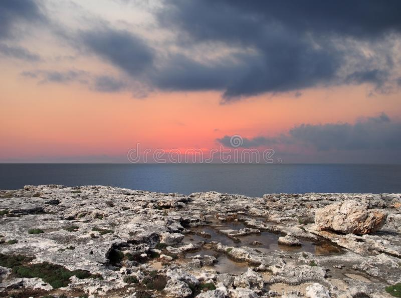Beautiful after sunset scene with glowing twilight sky illuminated with pink over a calm dark blue sea with white limestone clif royalty free stock images