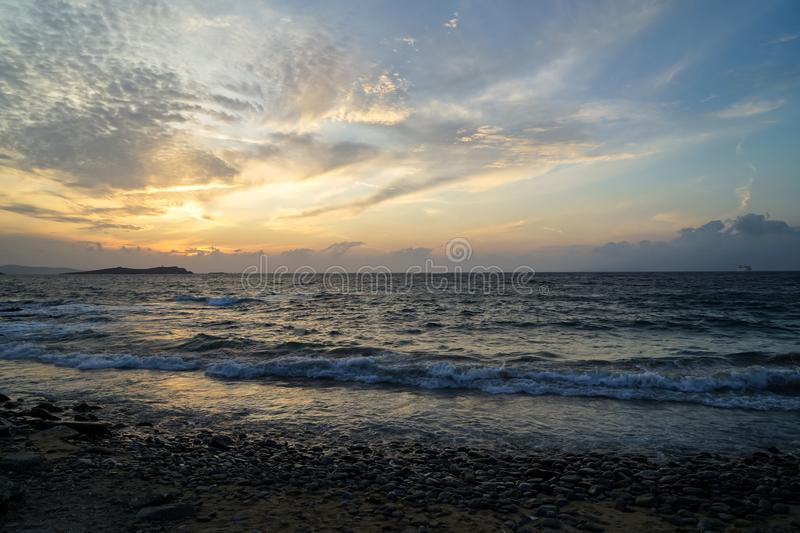Beautiful sunset scene wavy seaview and natural rock beach with beautiful shades of soft orange and blue sky and abstract cloud royalty free stock image