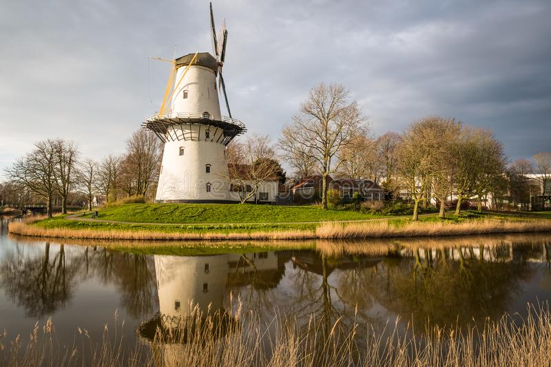 A windmill outside the city of Middelburg in the Netherlands. A beautiful sunset scene of a windmill on a canal from Middelburg, the Netherlands stock images