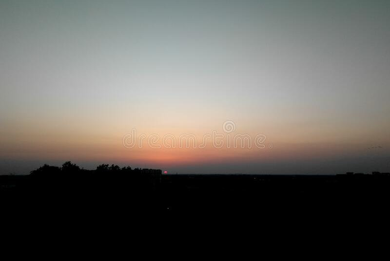 Beautiful sunset scenery view over the city, dusky orange sky and dark cityscape background, nature photography stock photos