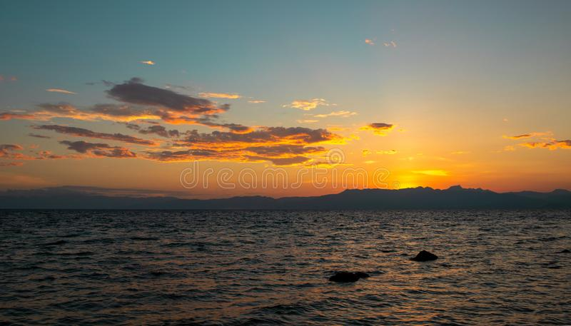 Beautiful sunset by sea. Orange sky and distant island landscape. Romantic evening seascape with sunset stock photography