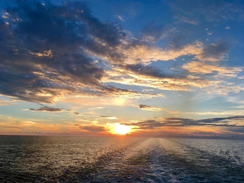 Dramatic sunset at sea. Beautiful sunset at sea with a sun going down behind horizon line royalty free stock photos