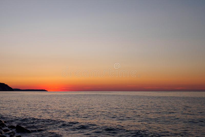Beautiful sunset and seascape. The bright orange sun descended to the horizon line. The last rays of the sun reflected in the dark. Beautiful sunset and seascape royalty free stock photography
