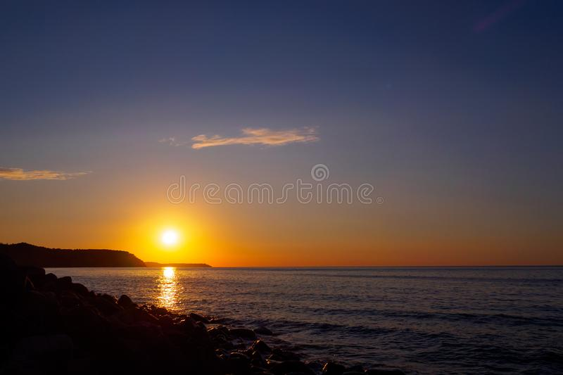 Beautiful sunset and seascape. The bright orange sun descended to the horizon line. The last rays of the sun reflected in the dark. Beautiful sunset and seascape royalty free stock photos