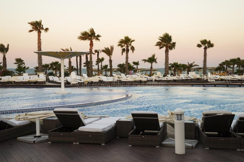A beautiful sunset seen from the hotel pool. Silhouettes of umbrellas and sun loungers by the pool. Sunset at the pool royalty free stock image