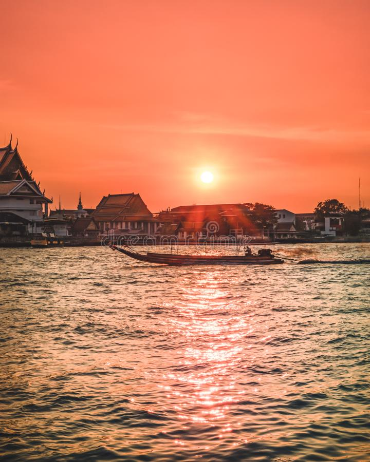 Beautiful sunset over the Bangkok river with a longtail boeat royalty free stock photography