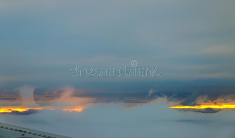 Beautiful sunset sky above clouds with dramatic view from airplane stock photography