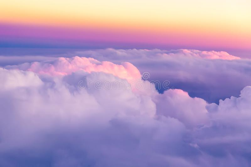 Beautiful sunset sky above clouds with nice dramatic light. View from airplane window stock image