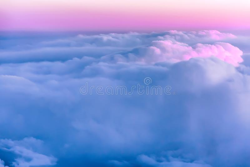 Beautiful sunset sky above clouds with nice dramatic light. View from airplane window.  stock photo