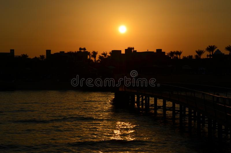Beautiful sunset sky above the sea beach in golden hour. Beautiful orange sunset sky above the sea beach in golden hour, silhouette coconut palm trees on beach royalty free stock photo