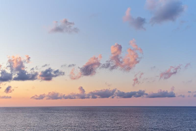 Beautiful sunset sky with cumulus clouds above sea surface with dramatic light. Beautiful sunset sky with bright multi-colored cumulus clouds above sea surface royalty free stock photo