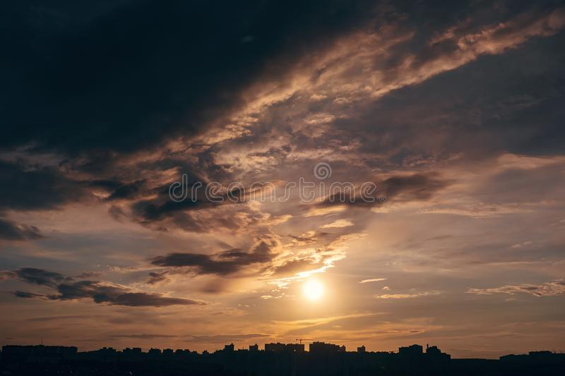 Beautiful sunset sky with dramatic clouds above silhouettes of city buildings royalty free stock photo