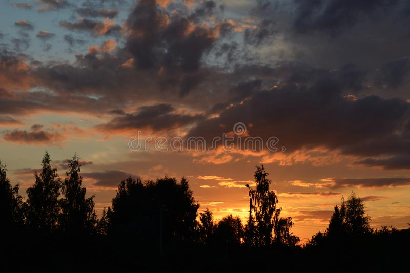 Beautiful sunset sky with dramatic light over the forest. Cloudscape in summer evening.  stock images