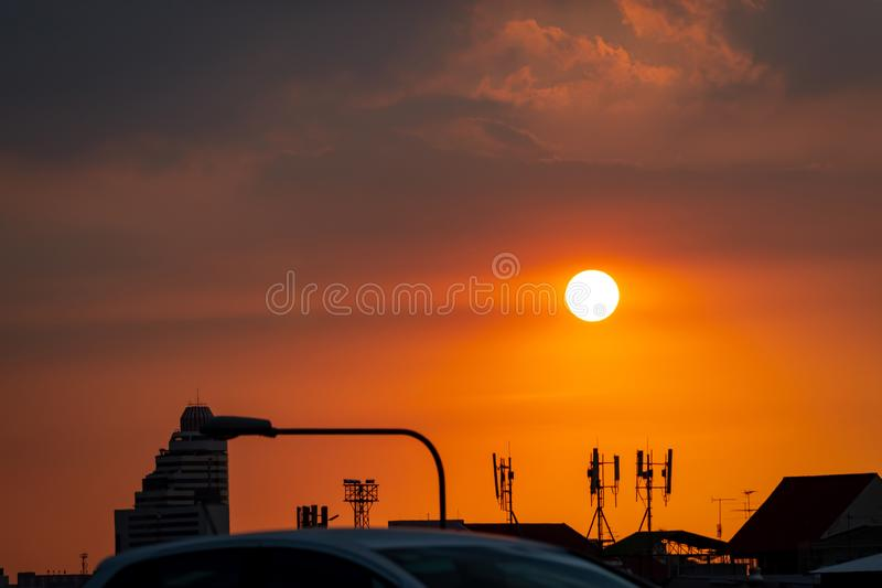Beautiful sunset sky over the city. Silhouette business building and telecommunication tower. Antenna on sunset sky background. Radio and satellite pole. View royalty free stock photos