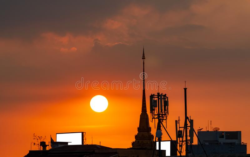 Beautiful sunset sky over the city. Silhouette temple building and telecommunication tower. Antenna on sunset sky background. stock photo