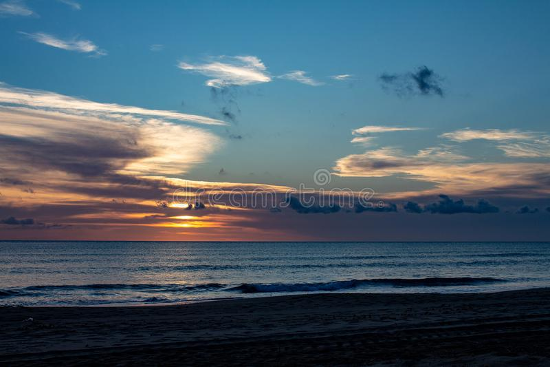 Beautiful sunset with the sky of varied colors. And clouds scattered on the water stock photo