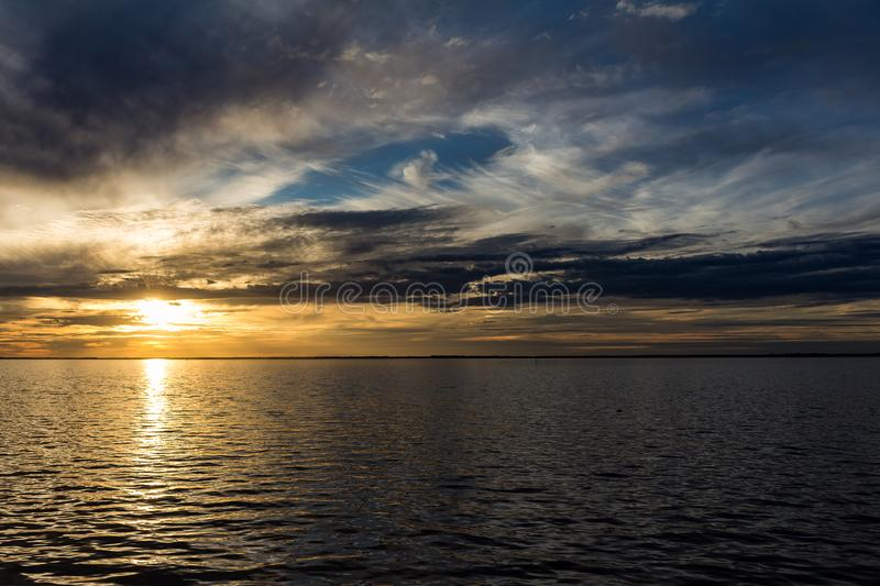 Beautiful sunset with the sky of varied colors. And clouds scattered on the water stock images