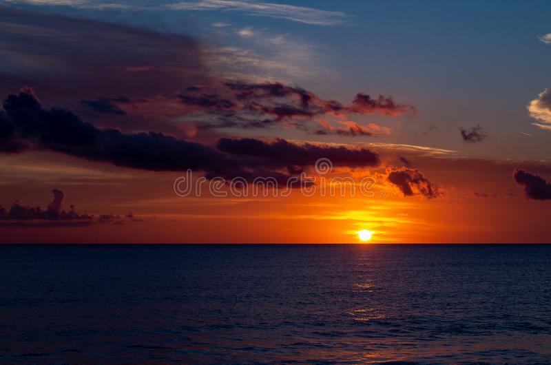 Beautiful sunset with the sky of varied colors. And clouds scattered on the water stock photography