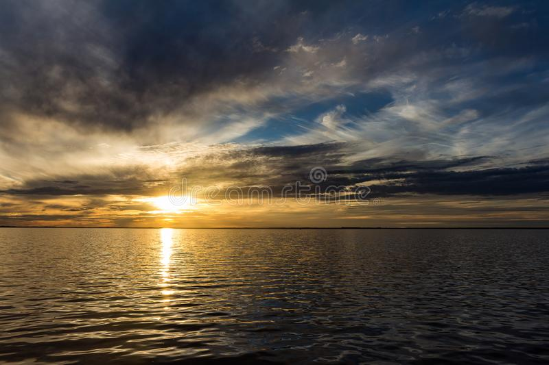 Beautiful sunset with the sky of varied colors. And clouds scattered on the water royalty free stock images
