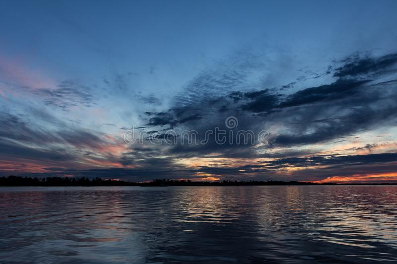 Beautiful sunset with the sky of varied colors. And clouds scattered on the water royalty free stock photography