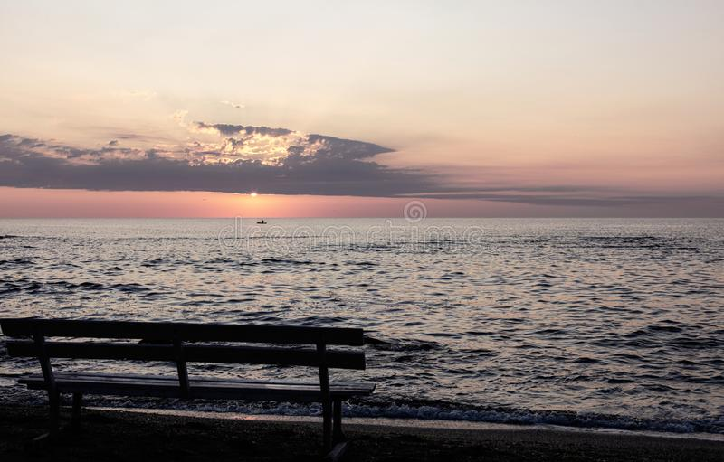 Beautiful sunset sunrise over the sea, beautiful waves and outlines of benches on the beach. Selective focus royalty free stock images