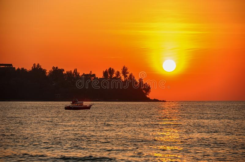 Beautiful sunset on a tropical beach. The ship sails in the last rays. royalty free stock photos