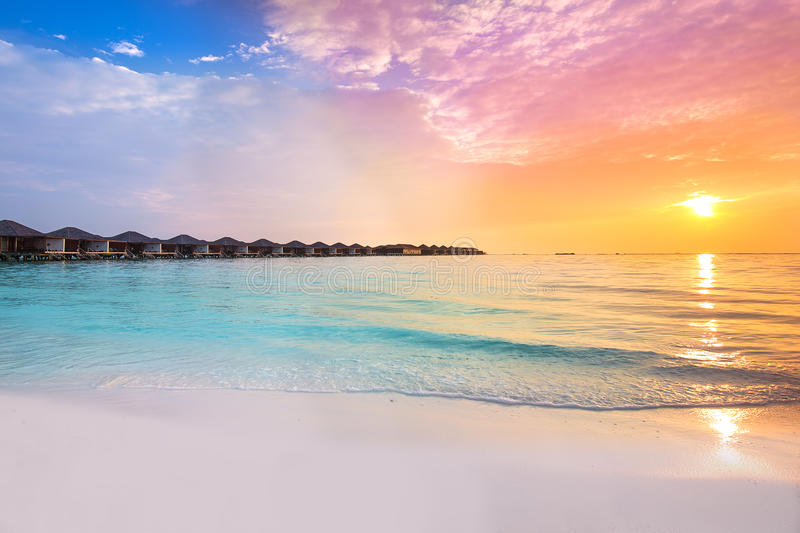 Beautiful sunset at tropical resort with overwater bungalows royalty free stock images