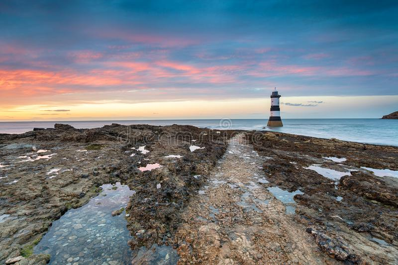 Trwyn Du Lighthouse at Penmon Point in Wales. A beautiful sunset at Trwyn Du lighthouse on Penmon Point near Beaumaris on Anglesey in Wales stock image
