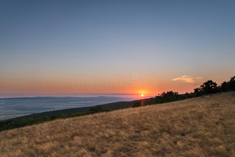 Beautiful sunset. View from the hill on the field, horizon and colorful sky stock image