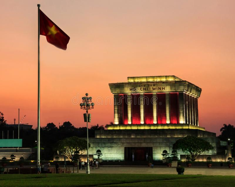 Beautiful Sunset view of Ho Chi Minh mausoleum with white uniform soldiers guarding in front Vietnamese National Flag, in royalty free stock photo