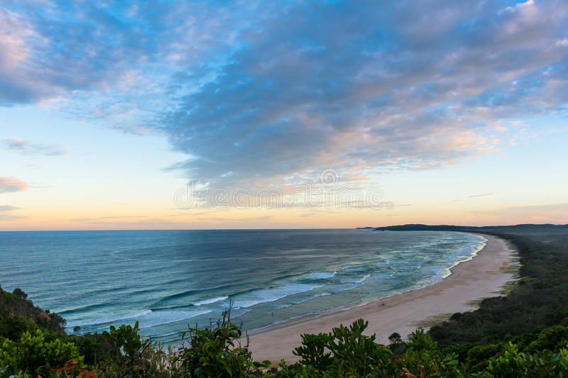The beautiful sunset and the view on Tallows beach in Byron Bay, Australia. The beautiful sunset view with cumulus cloudsand the view on Tallows beach in Byron stock photos