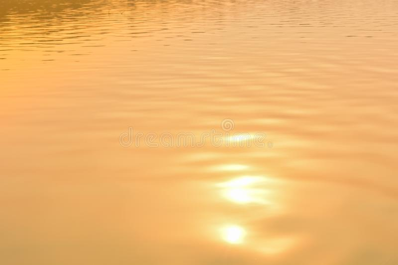 Beautiful sunset water background. The waves on the surface of the river. At twilight times and reflections. Golden and orange stock image