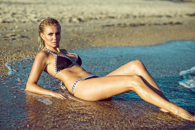 Beautiful suntanned glam blond woman with wet skin and hair lying on the beach and enjoying, her long legs washed by the sea. Waves. Resort and spa concept stock images