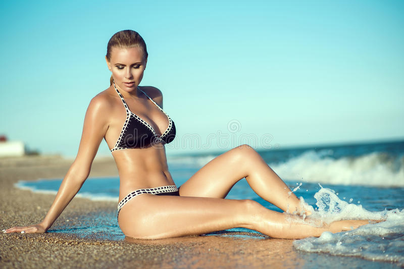 Beautiful suntanned glam blond woman with wet skin and hair sitting on the beach and enjoying, her long legs washed by the waves royalty free stock images
