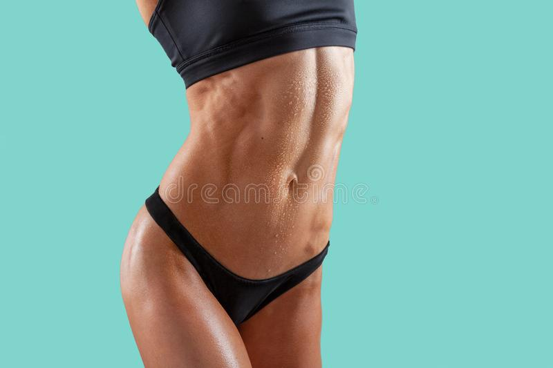 Beautiful super fit young woman showing off her perfect muscular ripped abs. Fitness model. Perfect Slim Body. Studio shot. royalty free stock image