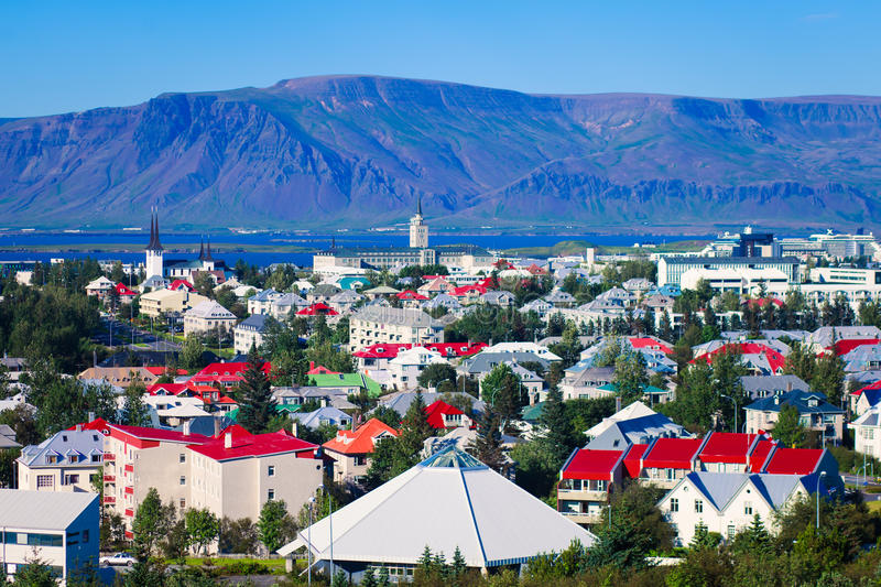 Beautiful super wide-angle aerial view of Reykjavik, Iceland with harbor and skyline mountains and scenery beyond the city, seen f. Rom the observation tower of royalty free stock image