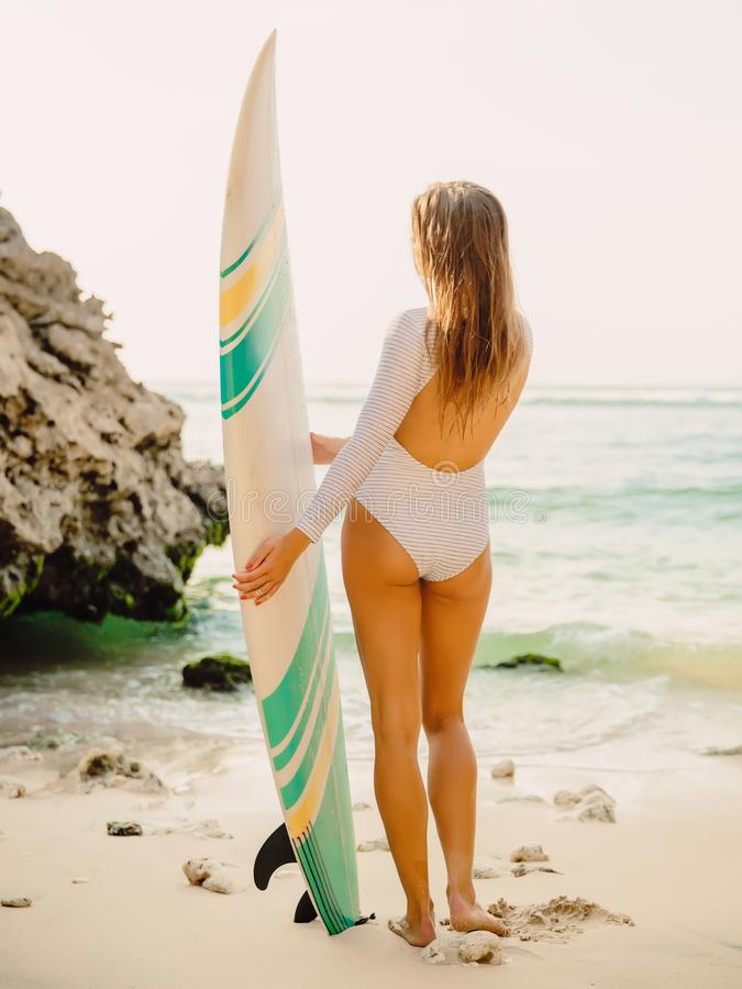 Beautiful surfer girl posing with surfboard on a beach. Beautiful surfer girl posing with surfboard on beach royalty free stock photography