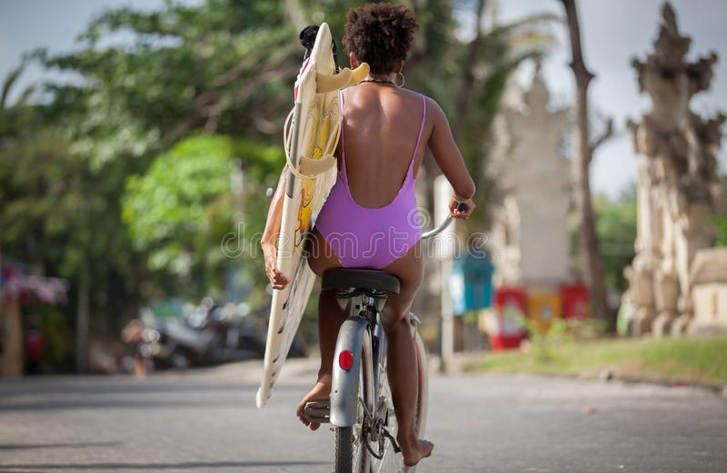 Beautiful surfer girl in purple bikini with afro hairstyle riding bicycle with one hand royalty free stock images