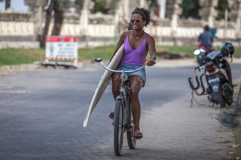 Beautiful surfer girl in purple bikini with afro hairstyle riding bicycle with one hand royalty free stock photography