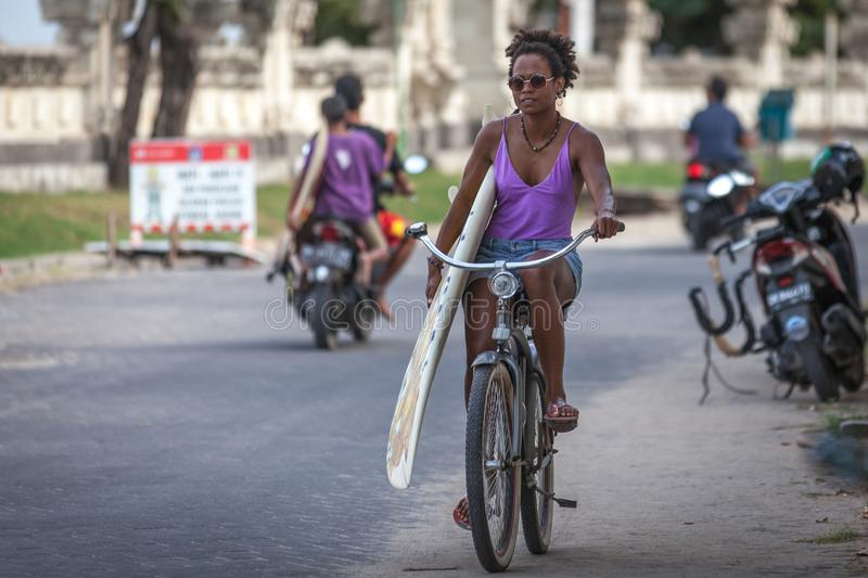 Beautiful surfer girl in purple bikini with afro hairstyle riding bicycle with one hand royalty free stock photos