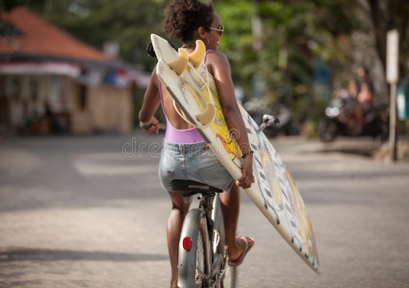 Beautiful surfer girl in purple bikini with afro hairstyle riding bicycle with one hand stock photo