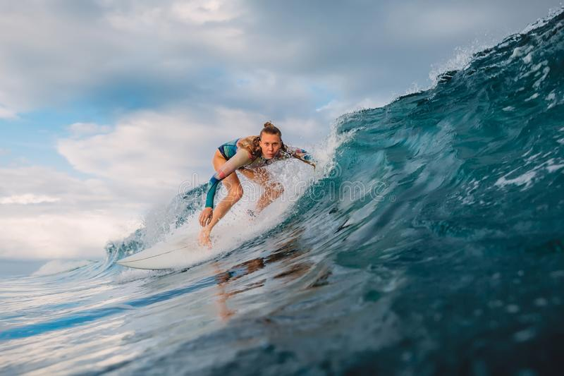 Beautiful surfer girl on surfboard. Woman in ocean during surfing. Surfer and barrel wave stock photos